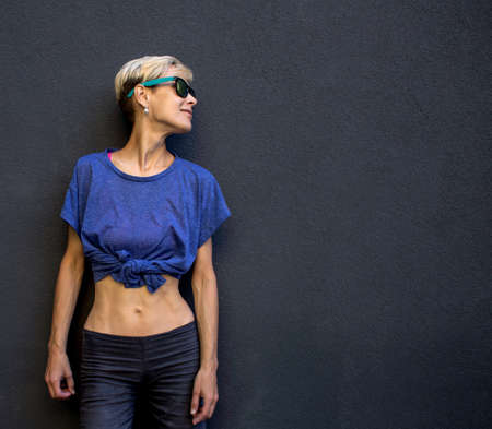 A girl with short hair stands against a dark gray wall, portrait of a blonde in sunglasses, a sexy woman. Imagens