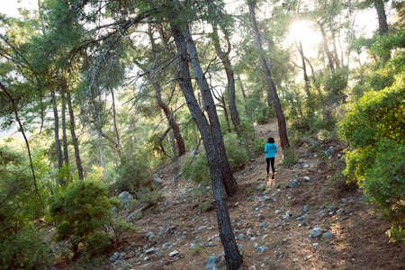 A woman runs along a mountain trail. Runner is training in the forest. Girl jogging in the park. Skyrunning.