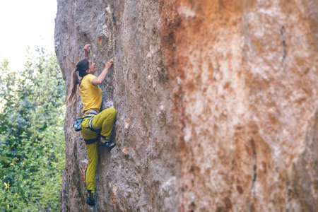 A girl climbs a rock on the background of the forest, The athlete trains in nature, Woman overcomes difficult climbing route, Strong climber, Extreme hobby, Rock climbing in Turkey.