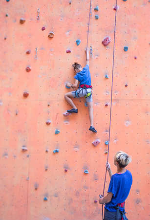 A coach teaches a child, a woman is belaying her son, a boy and his mother train together, children's training climbing, a boy climbs the wall, climbing gym Imagens - 152026716