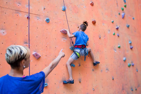 A coach teaches a child, a woman is belaying her son, a boy and his mother train together, children's training climbing, a boy climbs the wall, climbing gym Imagens - 152025905