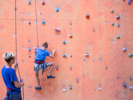 A coach teaches a child, a woman is belaying her son, a boy and his mother train together, children's training climbing, a boy climbs the wall, climbing gym Imagens