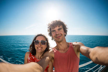 The family is sailing on a cruise ship, a girl with husband are standing at the fence on the ship and looking at the sea, traveling by ferry, a man with girlfriend take selfies on the ocean. Imagens