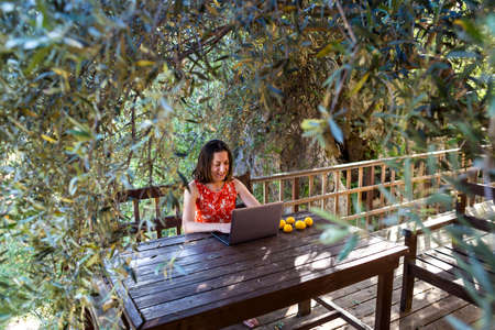 A woman in a red dress works on the terrace of a wooden house, A girl looks into a laptop, Distance education, Freelancer works on the veranda of the house, Remote work during quarantine.