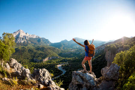 A woman with a backpack stands on top of a mountain with her hands up and admires the beauty of a valley, The girl travels to beautiful places, Reaching the goal, Beautiful landscape of Turkey. Imagens