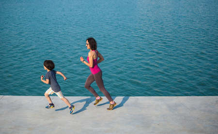 Jogging boy with mom. A child runs on distillation with his mother. A woman and her son run along the promenade along the water. Sport family. Healthy lifestyle.