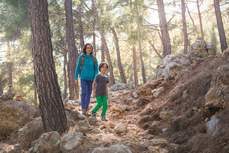 A woman walks with her son through the forest. The boy with his mother go hiking. A child with a backpack is in the park. Travel with children. The kid holds mom's hand. Imagens - 152342061