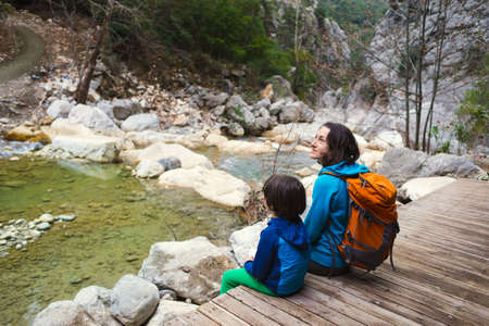 A woman with a backpack and a child are sitting on the shore of a mountain river, A boy travels with his mother, Hiking with children, Active holiday with a child.
