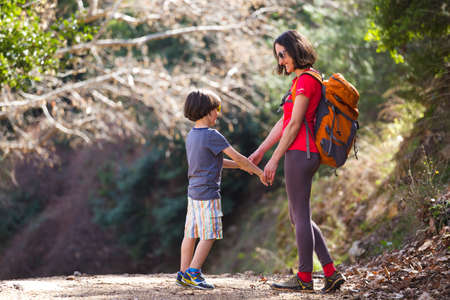 A woman walks with her son through the forest, The boy with his mother go hiking, A child with a backpack is in the park, Travel with children, The kid holds mom's hand, Mountain trail, Mothers Day. Imagens