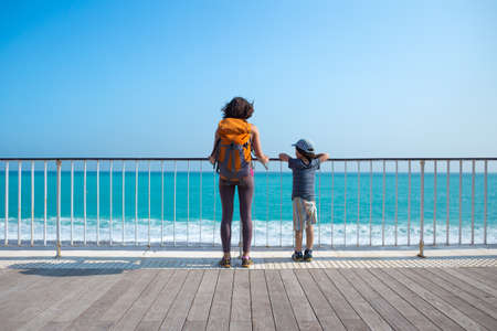 A boy with his mother stand on the promenade and look at the sea. A woman walking with her son on a city street. A young mother holds her baby's hand. Imagens