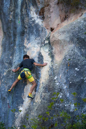 A strong man overcomes a difficult climbing route on a natural terrain. Rock climber trains on the Turkish rocks. Active lifestyle. Extreme hobby.