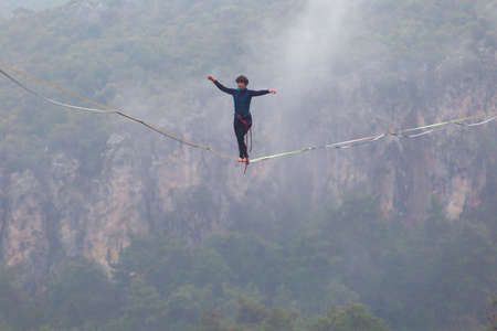 A woman is walking along a stretched sling. Highline in the mountains. Woman catches balance. Performance of a tightrope walker in nature. Highliner in the fog.
