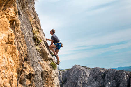 Rock climber on the background of mountains and sea. A man climbs on a rock. Training in nature. Active lifestyle. Extreme hobby. Strength and endurance in sports.