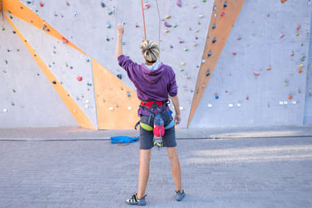 A girl trains on a climbing wall, happy woman climbed a route, preparation for overcoming a route in a climbing gym, equipment for belaying, a safety rope.