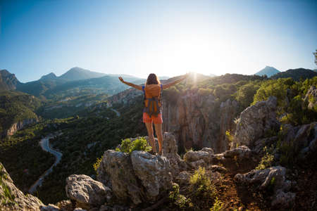 A woman with a backpack stands on top of a mountain with her hands up and admires the beauty of a valley, The girl travels to beautiful places, Reaching the goal, Beautiful landscape of Turkey.