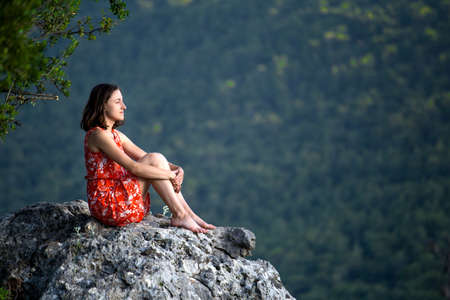 A girl in a red dress sits on a large rock on top of a mountain against the backdrop of a mountain valley, a trip to the picturesque places of Turkey.