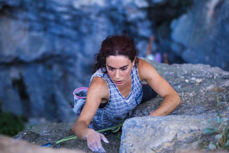 A woman is climbing in Turkey, Turkish woman climbs the rock, Extreme hobby, Overcoming a difficult climbing route, Overcoming the fear of heights, Climbing effort. Imagens