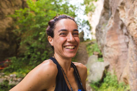 Portrait of a smiling rock climber. The woman is laughing. Emotional brunette is relaxing in nature. Imagens
