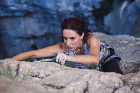 A woman is climbing in Turkey, Turkish woman climbs the rock, Extreme hobby, Overcoming a difficult climbing route, Overcoming the fear of heights, Climbing effort, Emotional girl. Imagens
