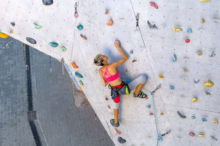 A woman climbs a climbing wall, a climber is training on artificial terrain, rock climbing in the city, a strong girl, sports in the city, safety in extreme sports.