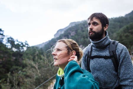 A man and a woman are surprised to see something in the distance during an excursion in the mountains. Hiking with backpacks in the mountains. Loving couple explores new places.