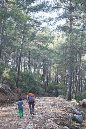 A woman walks with her son through the forest. The boy with his mother go hiking. A child with a backpack is in the park. Travel with children. The kid holds mom's hand. Imagens