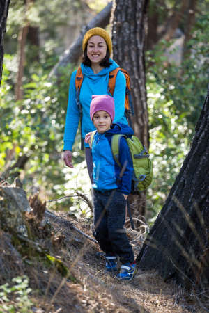 A woman walks with her son through the forest. The boy with his mother go hiking. A child with a backpack is in the park. Travel with children. The kid holds mom's hand. Mountain trail. Imagens