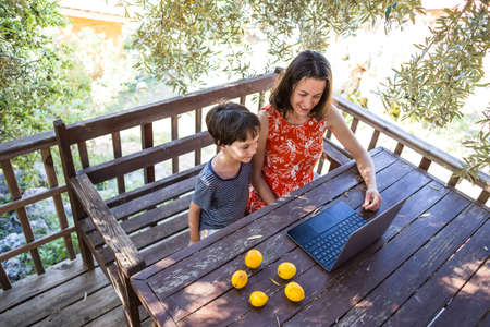 Mom with a child sits on the terrace of a wooden house and look at the laptop. A boy with his mother communicates with relatives on the Internet during quarantine. A woman with son in the courtyard.