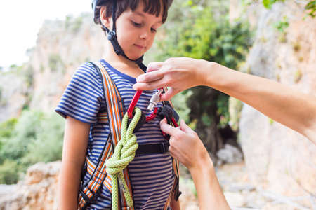 The instructor teaches the child to use climbing equipment, The boy is preparing to climb a rock, A woman shows a child how to use a carabiner for belaying, Mother ties the rope to the safety system. Imagens