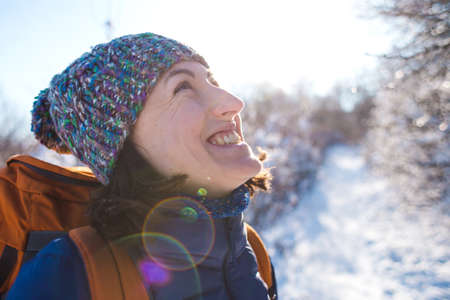 Portrait of a girl in a knitted hat. Smiling woman with a backpack on a background of a snowy forest. Woman on a winter hike. Winter ascent to the mountains.