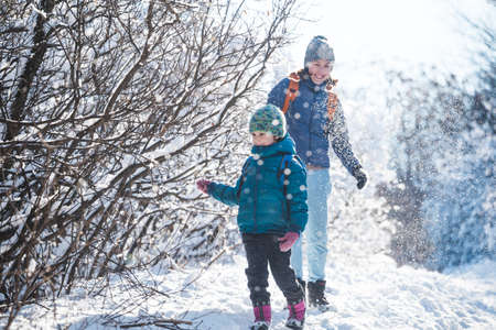 A boy plays snowball with his mother. A woman plays with her son in a snowy forest. Winter fun. A woman walks with a child in a winter park.