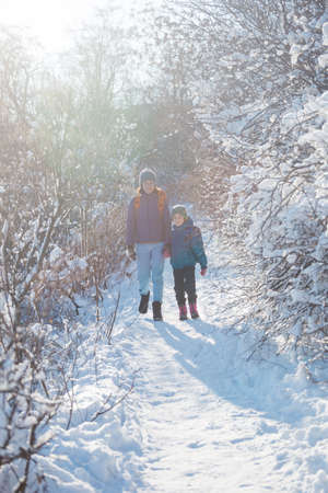 Woman with a child on a winter hike in the mountains. The boy travels with mother in the cold season. A child with a backpack walks with mother in a snowy park. Trekking with children. Winter trip.