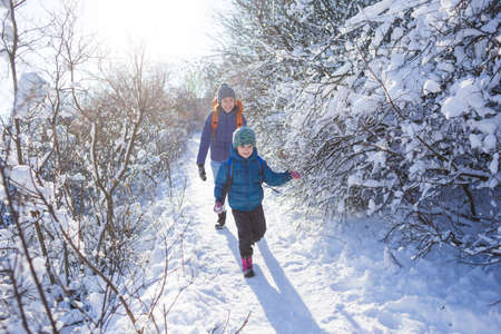 The child runs away from mom. A woman walks with a child in a winter park. The boy spends time with his mother. Mother's love. Walk through the snowy forest. Family walk. Imagens