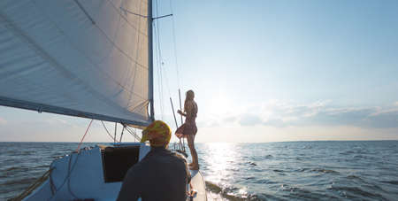 Romantic couple in love on sail boat traveling under sunlight on yacht, A man and a woman are on a sailing yacht. Reklamní fotografie