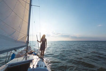 A girl in a dress stands on a sailing yacht, a woman admires the sunset from a yacht, a water trip.