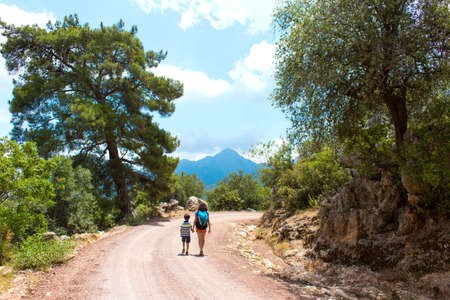 A woman with a backpack leads a child by the hand along a mountain trail, A boy travels with his mother. Hiking with children, Travel to the picturesque places of Turkey.