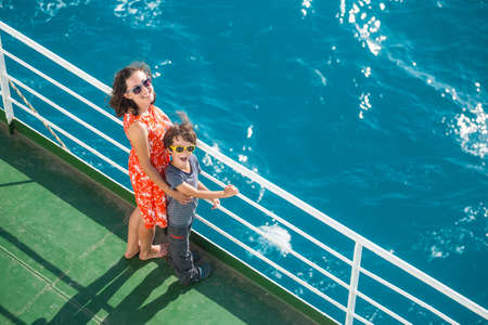 The family is sailing on a cruise ship, a mother with son are standing at the fence on the ship and looking at the sea, traveling by ferry, a boy with mom are sailing on a ship. Imagens