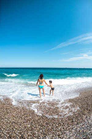 Woman with a child on the beach in Turkey, Mom and son go swimming in the sea, a boy and Mom relax on the ocean coast, beautiful sea waves.