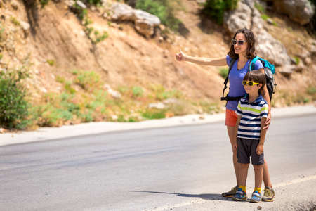 Woman with a child hitchhiking, The girl catches the car, Brunette with a backpack and young son waiting for transport, Hitchhiking in Turkey, The boy with his mother stands on a mountain road.