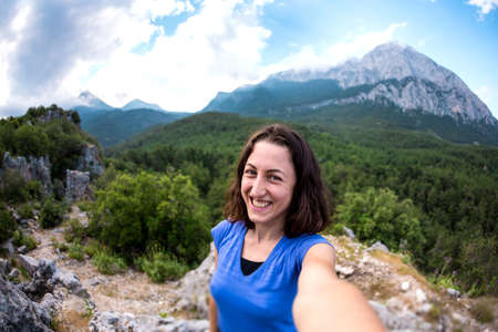 A woman takes a selfie on top of a mountain, a girl is photographed against a background of a mountain valley, a trip to the picturesque places of Turkey. Imagens