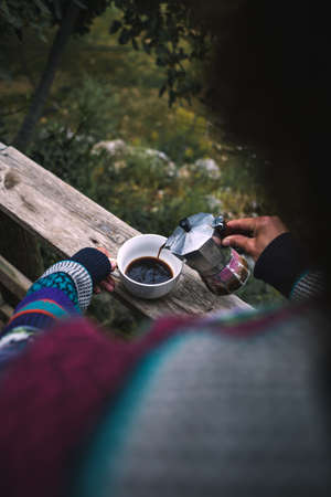 A woman pours coffee into a white cup from a geyser coffee maker, Morning hot drink in nature, Girl is making coffee on the porch of a wooden house.