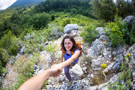 A woman with a backpack travels in the mountains, Helping hand, A man helps a girl to climb a hill, Travel to the picturesque places of Turkey.