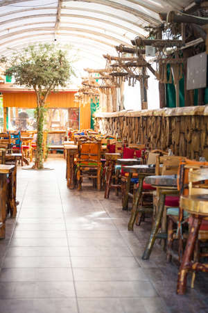 Interior of a turkish cafe. Wooden chairs and tables in a coffee shop. Eastern cuisine. Coffee shop room without people.