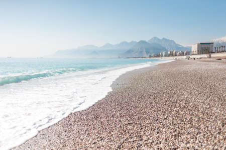 Turkish beach without people. Mediterranean Sea in Turkey. Ocean waves and coastal sand. Resort on the background of mountains and sky. Deserted beach. Imagens