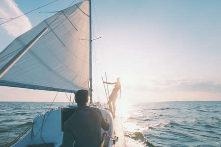 Romantic couple in love on sail boat traveling under sunlight on yacht, A man and a woman are on a sailing yacht.