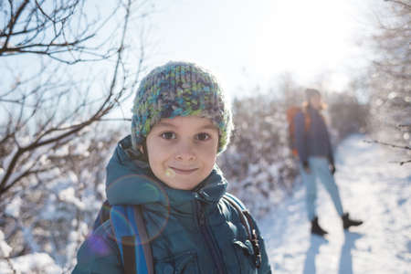 Woman with a child on a winter hike in the mountains, The boy travels with mother in the cold season, A child with a backpack walks with mother in a snowy park, Trekking with children, Winter trip.