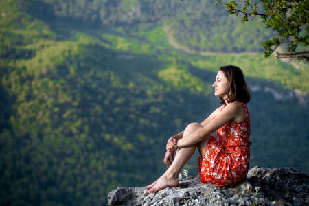 A girl in a red dress sits on a large rock on top of a mountain against the backdrop of a mountain valley, a trip to the picturesque places of Turkey. 版權商用圖片