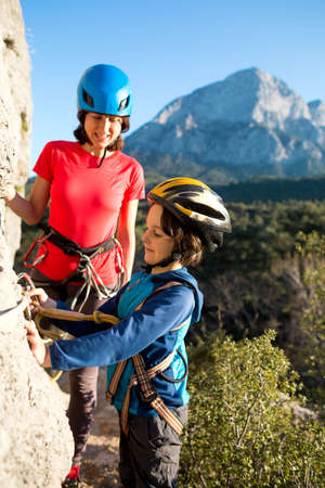 The instructor teaches the child to use safety equipment. The boy in helmet goes through Via Ferrata. A woman checks how a child learns to use a carbine for belaying. Mountain tourism for children.