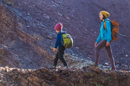 A woman is traveling with a child, Mom and son in the mountains, Climb to the top of the mountain with children, A boy with a backpack walks in the forest with his mother, Active vacations.
