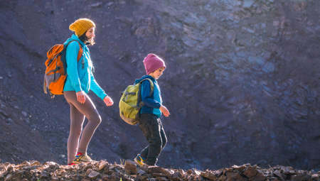A woman is traveling with a child. Mom and son in the mountains. Climb to the top of the mountain with children. The boy with the backpack climbed to the top. Active vacations. 免版税图像